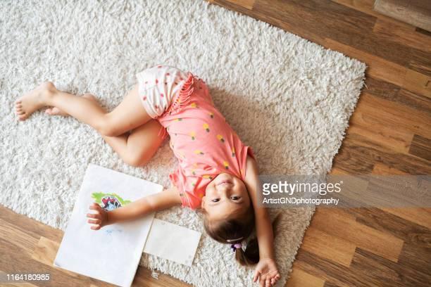 piccola ragazza carina sdraiata sul tappeto a casa e sorridente. - moquette foto e immagini stock