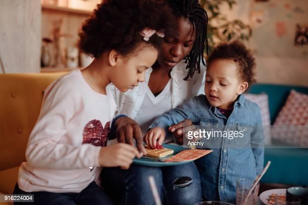 かわいい女の子ワッフルから果実を取って - interracial cartoon ストックフォトと画像