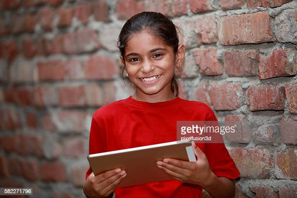 Little cute happy girl holding tablet