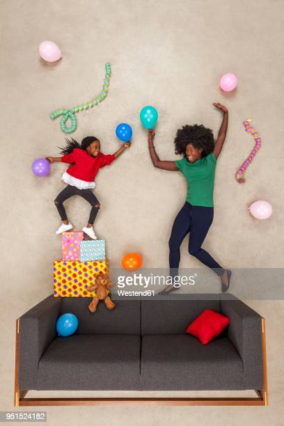 little daughter celebrating birthday party, dancing with her mother - beige background stock pictures, royalty-free photos & images