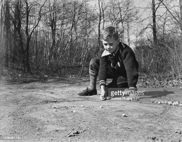 Little Donnie Irwin playing a game of marbles USA 3rd April 1938