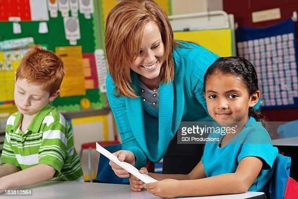 Little Elementary Girl Receiving Test Paper Back From Teacher