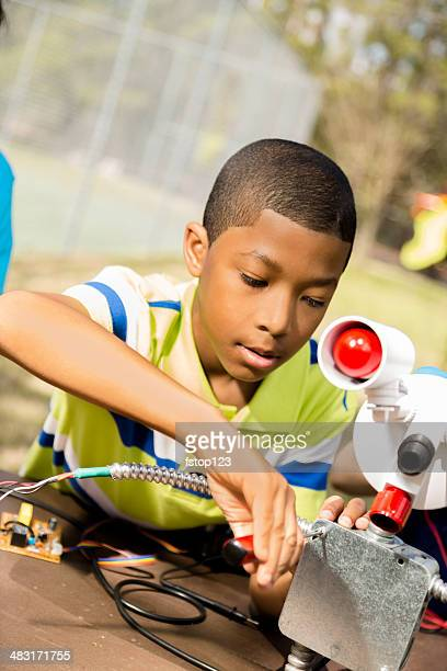 Little engineer!  Elementary child works on 'robot' he created.