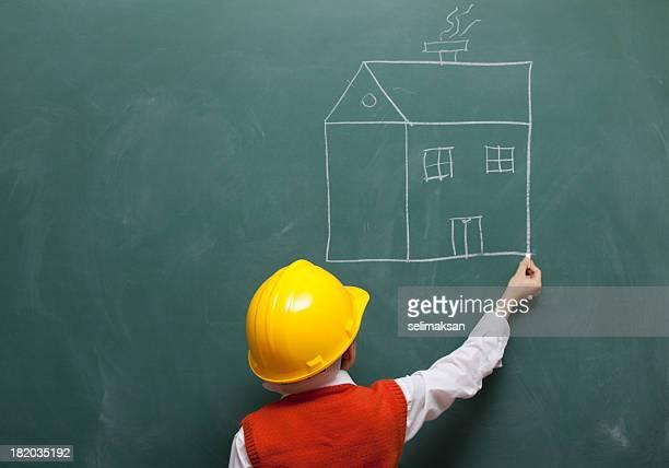Little engineer with helmet drawing a house on blackboard
