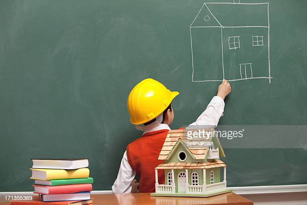 Little engineer with helmet drawing house on blackboard