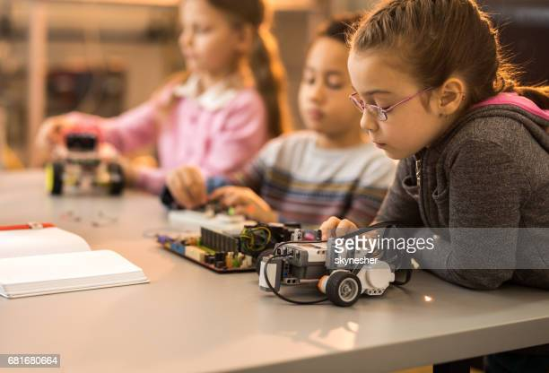 Little engineer working on innovative robots with her friends in laboratory.