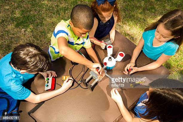 Little engineers!  Ethnic elementary children collaborate on 'robot' they created.