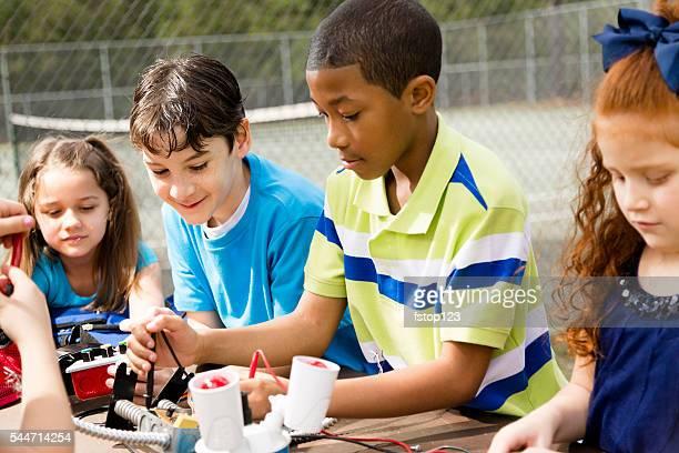 Little engineers! Multi-ethnic elementary children collaborate on 'robot' creation.