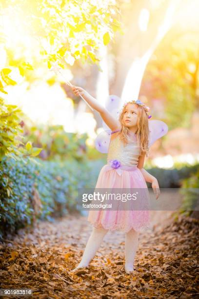 little fairy with magic wand looking upwards - fairy stock pictures, royalty-free photos & images