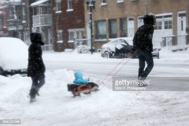 Little family walking under the snow storm in Montreal