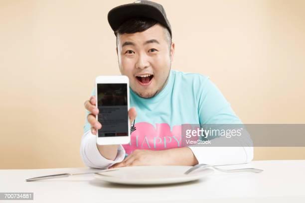 Little fat man using a cell phone