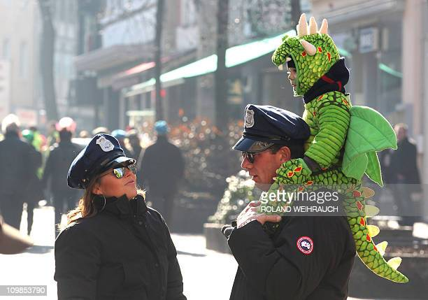 A little fool dressed as a dragon celebrates with his parents dressed as policemen in the streets of Duesseldorf western Germany after the official...