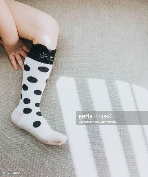 little foot wearing spotty knee sock - femur fotografías e imágenes de stock