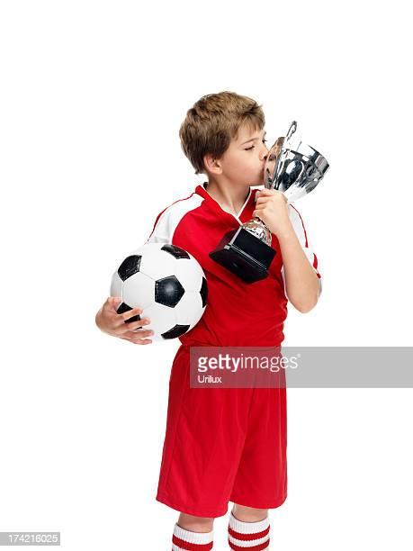 小さなフットボールチャンピオンとしてトロフィーにキスをする彼の受賞