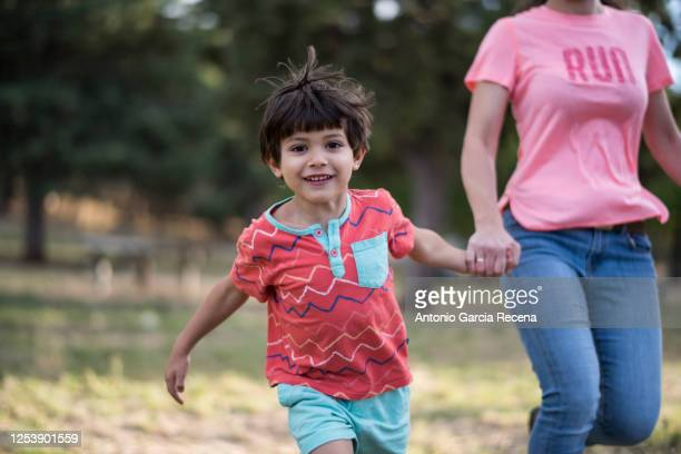 little four years old kid running in outdoors park with his mother holding hand - southern european descent stock pictures, royalty-free photos & images