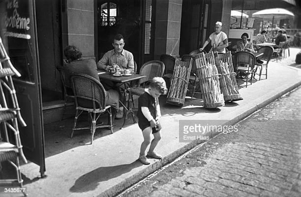 A little French boy in Montmartre uses the gutter outside a cafe to relieve himself