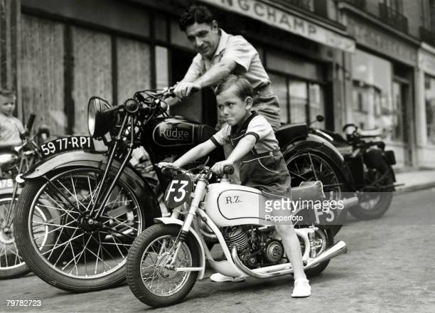 A little French boy watched by his father tries out a tiny motorbike on a Paris street 19th July 1951