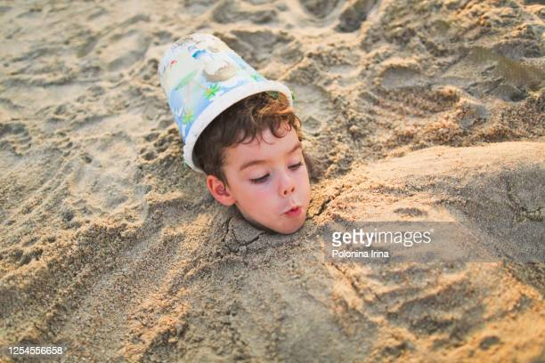 little funny boy playing on the sea beach. - enterrar imagens e fotografias de stock