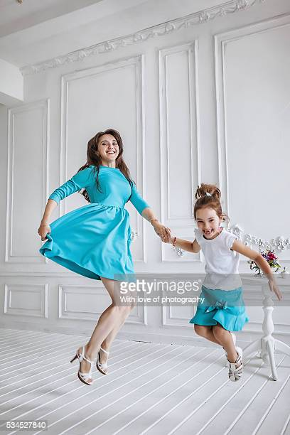 little girl about 10 years old and her smiling beautiful mother jumping together, family