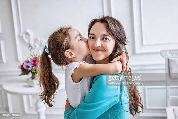 little girl about 10 years old embracing and kissing her smiling beautiful mother both looking at camera, family - happy mothers day mom stock-fotos und bilder
