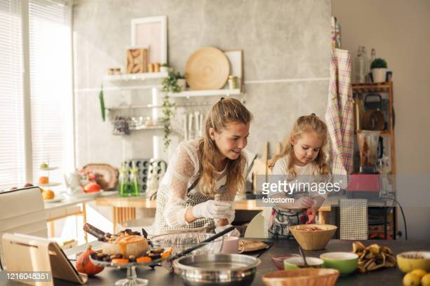 little girl adding bananas to a healthy vegan sweet preparation - wide shot stock pictures, royalty-free photos & images