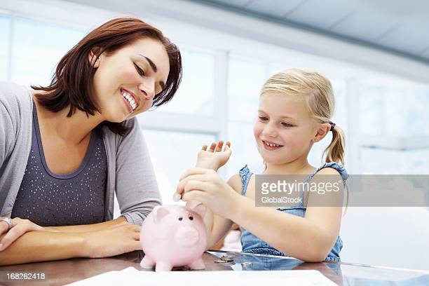 Little girl adding money to piggy bank