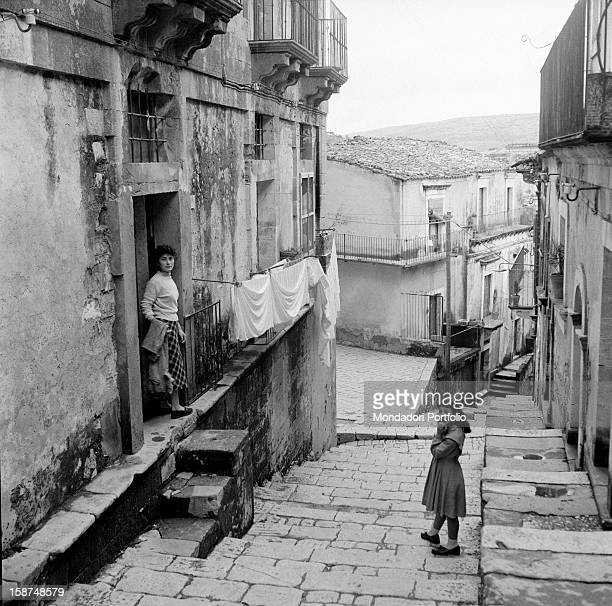 A little girl and a woman standing on the entrance of their house in the neighbourhood called Ragusa Ibla Ragusa 1955