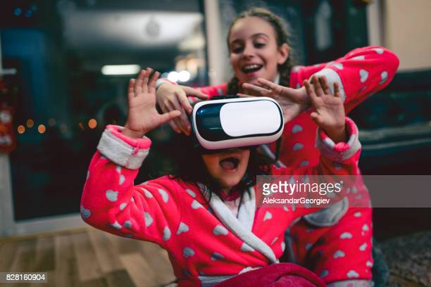 Little Girl and Bigger Sister Having Fun with Virtual Reality Simulator and Gesturing