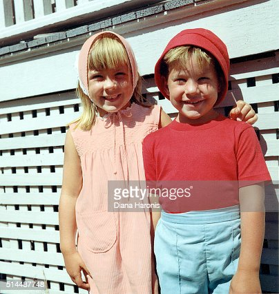 A little girl and boy are standing together near an old porch.