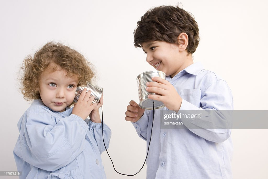 Little Girl And Boy Communicating Via Tin Can Phone : Stock Photo