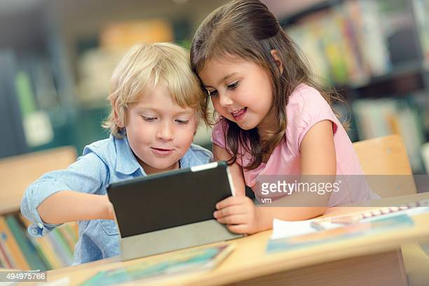Little girl and boy in library