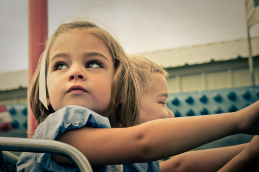 Little girl and boy on carnival ride - gettyimageskorea