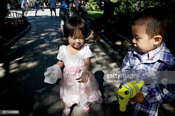 Little girl and boy play with bubbles in Zizhuyuan Park in Beijing China This park is well known as a place where middle aged or elderly Chinese come...