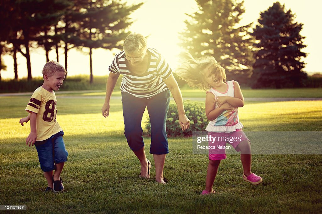 Little girl and boy playing tag with their grandma : Stock Photo