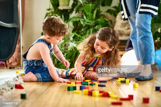 little girl and boy playing together with wooden blocks - playing stock pictures, royalty-free photos & images