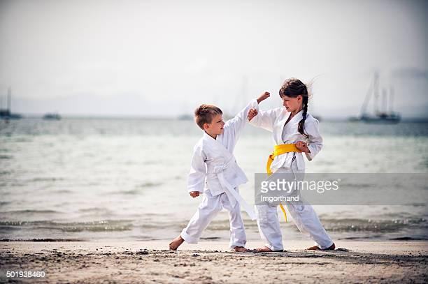 Petite fille et garçon pratiquant le karaté sur la plage