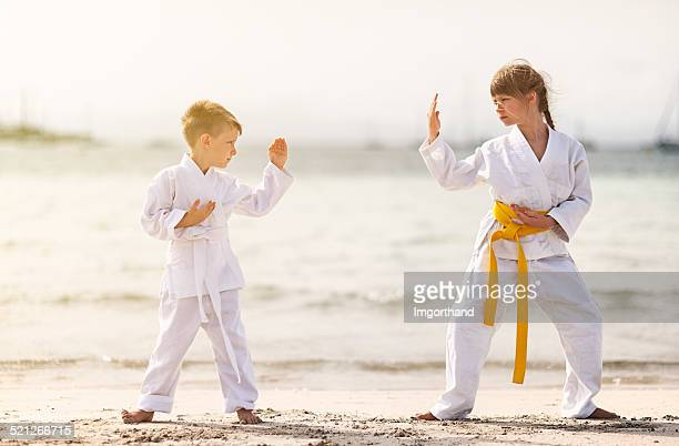 little girl and boy practicing karate on the beach - imgorthand stock photos and pictures