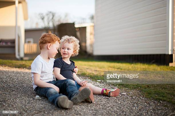 Little girl and boy sitting on gravel path