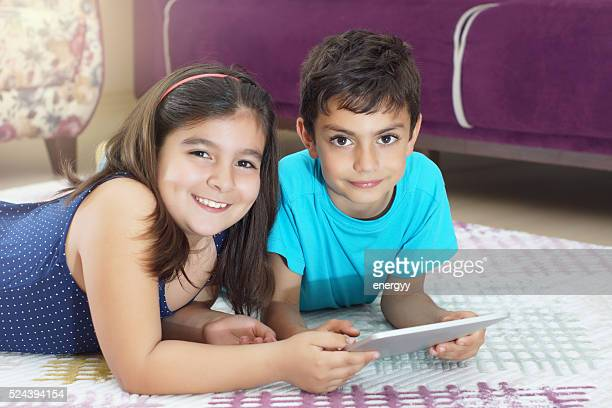 little girl and boy using tablet computer on the carpet - fat girls stock photos and pictures