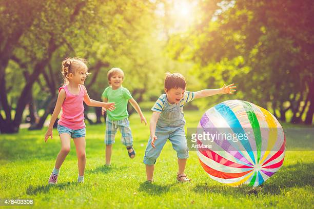 little girl and boys playing with ball - playing stock pictures, royalty-free photos & images