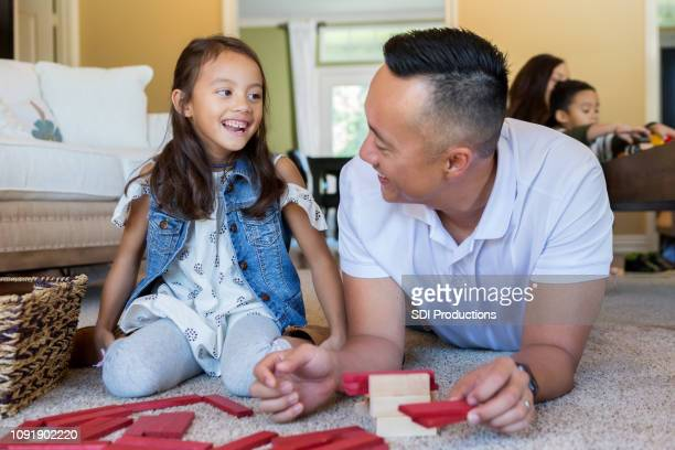 little girl and father enjoy quality time at home - lying on front stock pictures, royalty-free photos & images