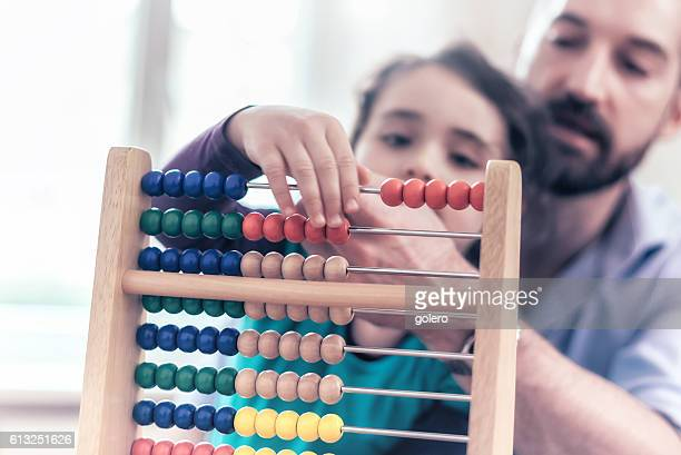 little girl and father learning calculating with abacus at home