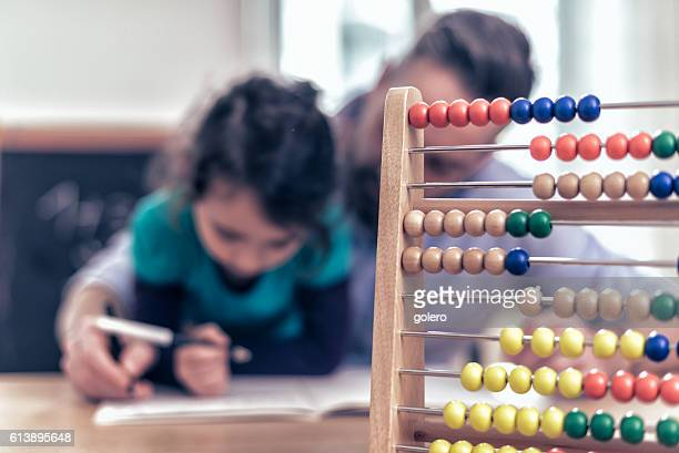 little girl and father learning calculating with abacus together