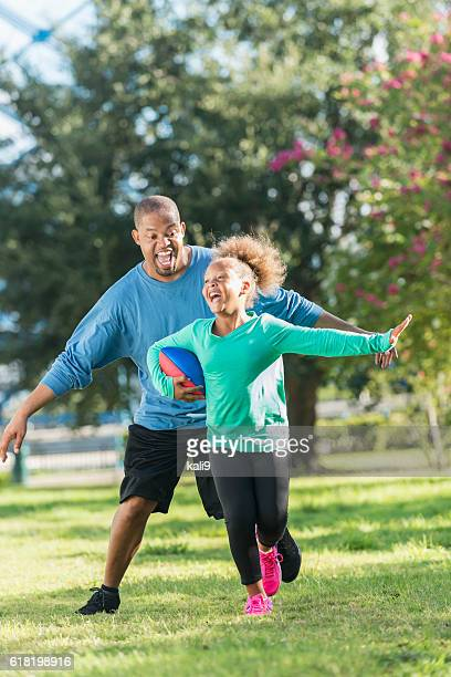 Little girl and father playing in the park with ball