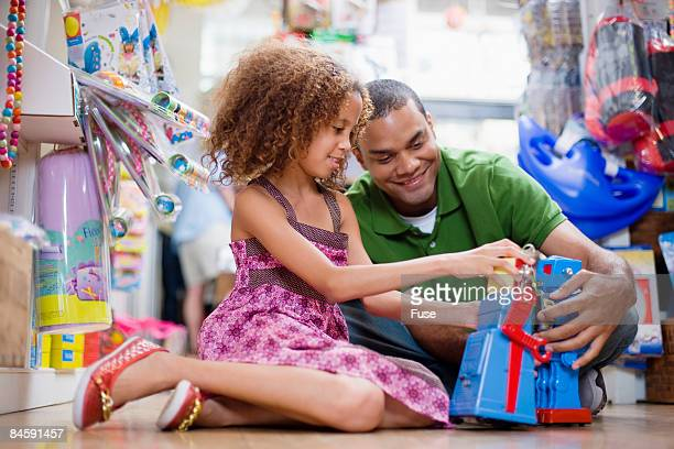 Little Girl and Father Playing with Toy Robots