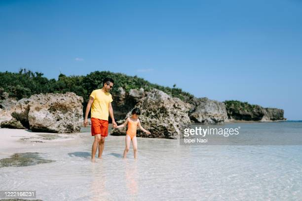 little girl and father walking on tropical beach, okinawa, japan - ippei naoi stock pictures, royalty-free photos & images