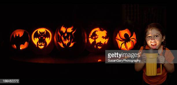Little Girl and Glowing Carved Pumpkins