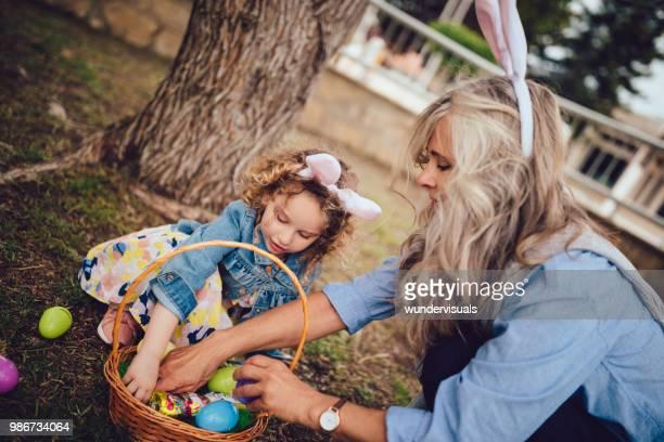 Little girl and grandmother during Easter egg hunt in park