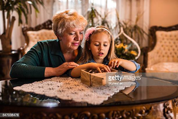 Little girl and grandmother looking at jewelry box at home.