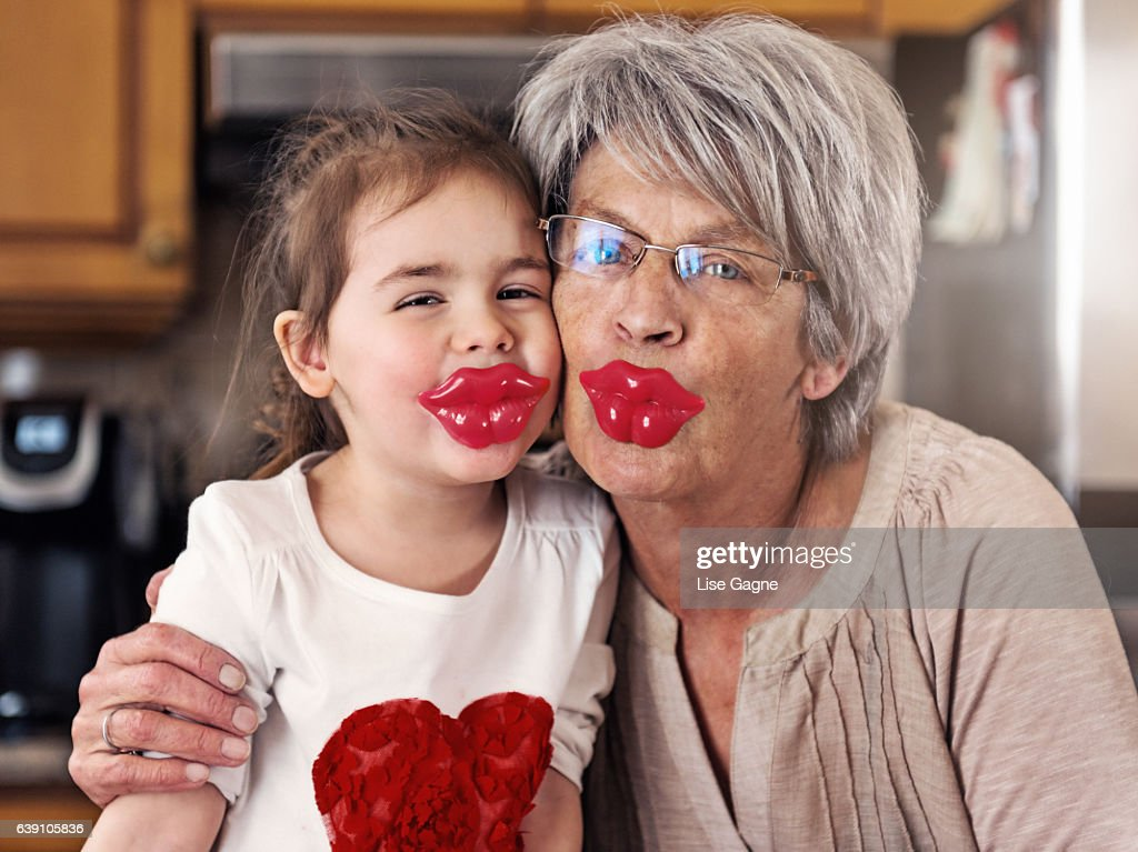 Little girl and grandmother posing with big lips lollypop : Foto de stock